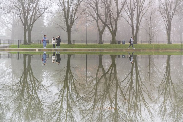 People are reflected in the Lincoln Memorial Reflecting Pool during a foggy day in Washington on December 17, 2019. (Photo by Salwan Georges/The Washington Post)