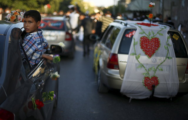 A Palestinian boy looks out of a car during a mass wedding for 150 couples in Beit Lahiya town in the northern Gaza Strip July 20, 2015. (Photo by Suhaib Salem/Reuters)