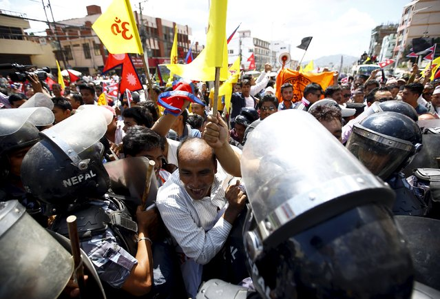 Hindu activists chant slogans as they try to break through the restricted area during the protest rally marching towards the parliament demanding Nepal to be declared as Hindu State in the new constitution, in Kathmandu August 3, 2015. (Photo by Navesh Chitrakar/Reuters)