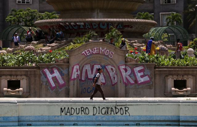 """Anti-government protesters begin gathering at Altamira Plaza, defaced with messages that read in Spanish; """"We're hungry. Maduro Dictator"""", in Caracas, Venezuela, Monday, June 26, 2017. More than 70 people have been killed during almost 90 days of protests seeking President Nicolas Maduro's removal. (Photo by Fernando Llano/AP Photo)"""
