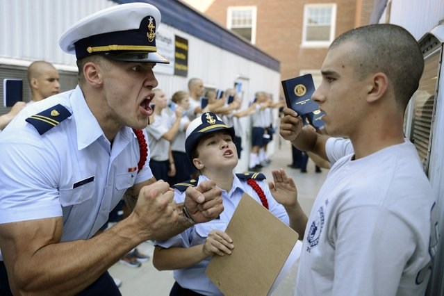 "United States Coast Guard Academy Cadets Second Class Aurimas Juodka, left, and Sheila Bertrand get in the face of ""swab"" Kevin Lennox as Bravo Company finishes at the barber shop and mailroom during R-Day, the reporting-in day that marks the beginning of the 7-week ""Swab Summer"" for the class of 2018 Monday, June 30, 2014, in New London, Conn. (Photo by Sean D. Elliot/AP Photo/The Day)"