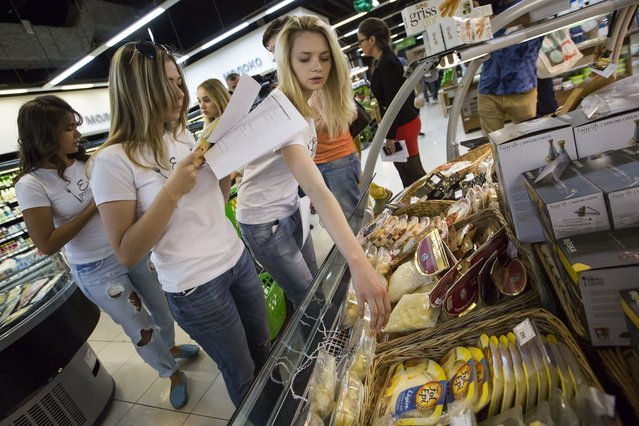"""In this photo taken on Tuesday, August 4, 2015, a group of activists, members of """"Eat the Russian food"""" movement, check food at a Moscow food store in Moscow, Russia. Russia has marked the one-year anniversary of its ban on Western agricultural products with an order to destroy contraband food, a move that has raised controversy amid the nation's economic downturn. (Photo by Alexander Zemlianichenko/AP Photo)"""