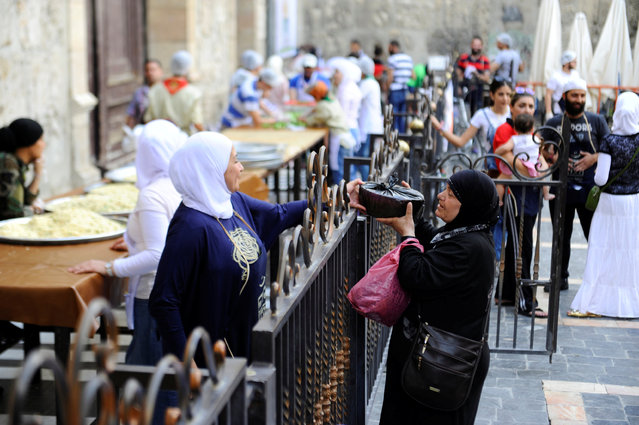 A woman receives food given out as Iftar meals by a member of Saaed group for the poor and internally displaced Syrians during the month of Ramadan in Damascus, Syria June 18, 2016. Iftar (or Fatoor) is the evening meal when Muslims end their daily Ramadan fast at sunset. Muslims break their fast at the time of the call to prayer for the evening prayer. (Photo by Omar Sanadiki/Reuters)