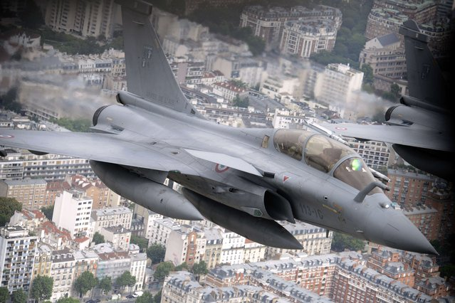 A picture taken on July 14, 2014 from a Boeing C135 refueling tanker shows two French Rafale fighter planes, flying over the French capital during the annual Bastille Day military parade on the Champs-Elysees in Paris. France has issued an unprecedented invitation to all 72 countries involved in World War I to take part in its annual Bastille Day military parade. (Photo by Franck Pennant/AFP Photo)