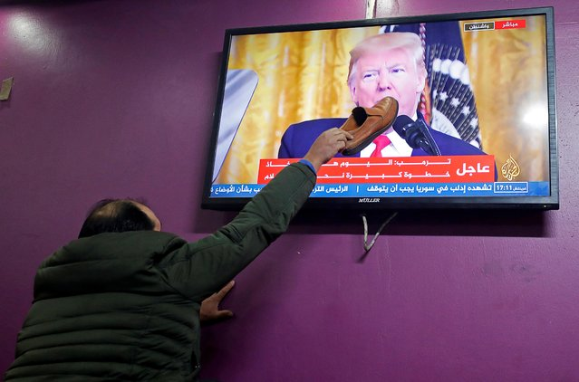 A Palestinian man places a shoe on a television screen broadcasting the announcement of Mideast peace plan by U.S. President Donald Trump, in a coffee shop in Hebron in the Israeli-occupied West Bank on January 28, 2020. (Photo by Mussa Qawasma/Reuters)