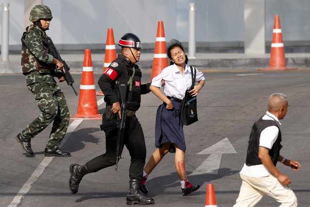 Soldiers evacuate a hostage from a mass shooting scene at the Terminal 21 shopping mall in Nakhon Ratchasima, Thailand, 09 February 2020. According to media reports, at least 21 people were killed, and as many as 30 wounded after a Thai soldier, identified as 32-year-old Jakraphanth Thomma, went on a shooting rampage with a M60 machine gun in the city of Nakhon Ratchasima, also known as Korat. Thomma held an unknown number of people hostage within the Terminal 21 shopping mall for around 17 hours before being shot and killed in a police operation. (Photo by Rungroj Yongrit/EPA/EFE)