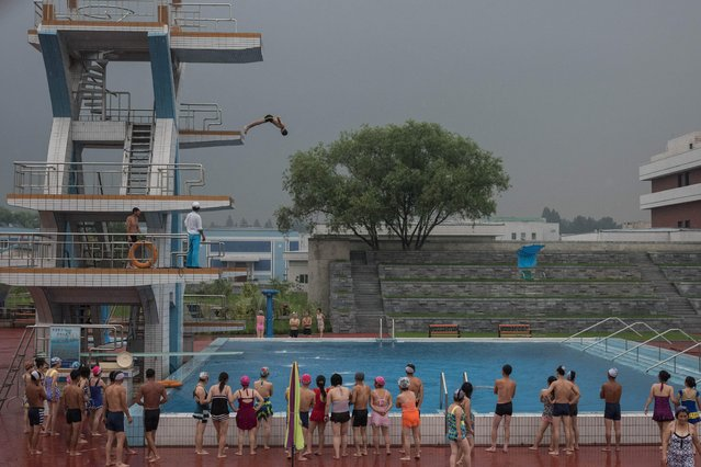 Swimmers watch as a man performs a dive from a platform at a water park in a leisure complex in Pyongyang on July 21, 2017. (Photo by Ed Jones/AFP Photo)