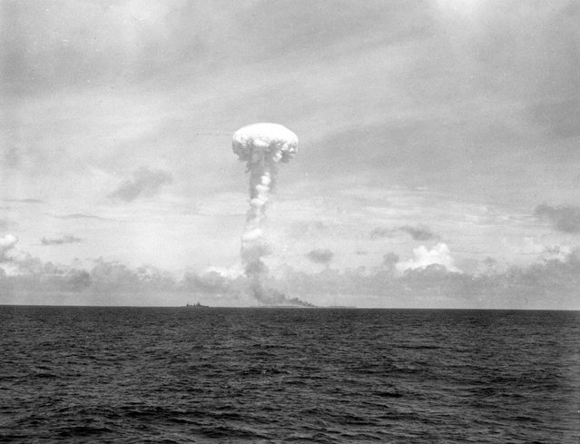 Navy shells hit jackpot, raise extremely high plume of smoke (note tiny ship on the left)