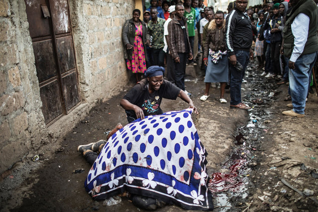 The mother of a man shot in the head allegedly by Kenyan police uses a blanket to cover her son's body in an alley of Mathare slum in Nairobi, on August 9, 2017, as unrest broke out a day after general elections. (Photo by Marco Longari/AFP Photo)