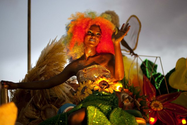"""A carnival queen greets people from the top of a parade float during the """"Carnival of Flowers"""" celebrations in Port-au-Prince, Haiti, on Jule 29, 2014. Thousands of revelers poured into the downtown area for the three-day celebration President Michel Martelly has revived from the Duvalier era. (Photo by Dieu Nalio Chery/Associated Press)"""