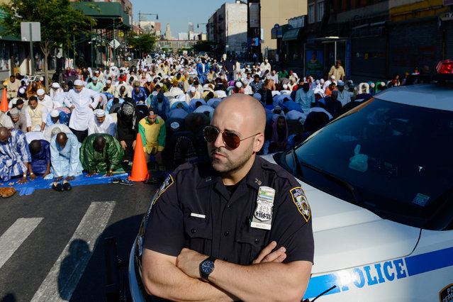 A New York City police officer stands guard as Muslims pray during the Eid holiday that marks the end of the Muslim holy month of Ramadan in the Brooklyn borough of New York City, July 6, 2016. (Photo by Stephanie Keith/Reuters)