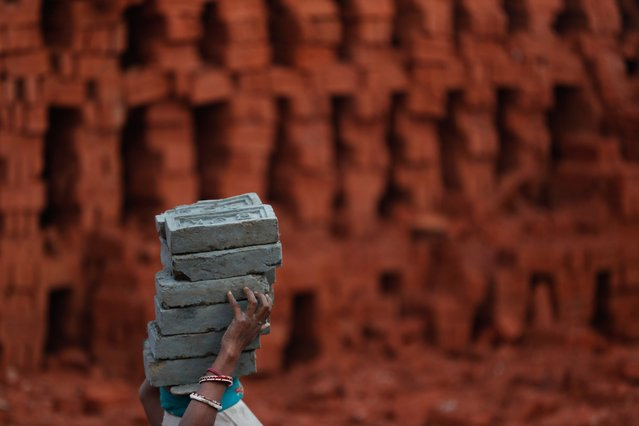 A Indian migrant woman worker carries bricks at a brick factory on the outskirts of Kathmandu, Nepal, Thursday, January 9, 2020. Thousands of workers from neighboring India and other parts of Nepal come to the Kathmandu valley to work in brick factories during the dry winter season. (Photo by Niranjan Shrestha/AP Photo)