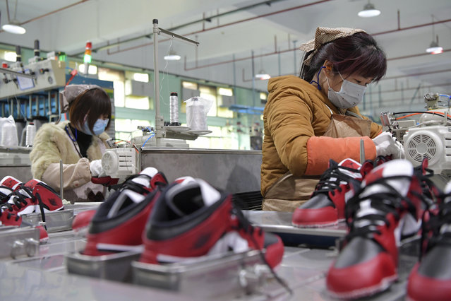 In this photo taken on February 22, 2020 and released by Xinhua News Agency, workers wear mask as they manufacture shoes at a factory in the town of Xiangtang, Nanchang county in eastern China's Jiangxi Province. Factories in China that make the world's smartphones, toys and other consumer goods are trying to protect their employees from a virus outbreak as they resume production. Manufacturers are buying masks by the thousands and jugs of disinfectant. The ruling Communist Party has told local officials to help reopen factories that were idled by the most intensive anti-disease controls ever imposed. (Photo by Peng Zhaozhi/Xinhua via AP Photo)