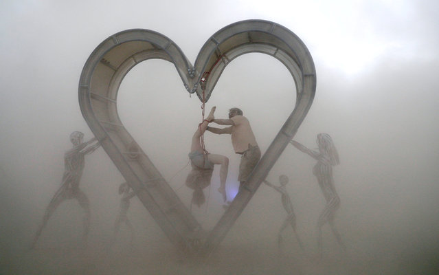 "Burning Man participants perform a shibari rope scene during a driving desert dust storm inside the heart of the ""Identity Awareness – Family"" art project created by artist Shane Pitzer on the 2nd day of the annual Burning Man arts and music festival in the Black Rock Desert of Nevada, U.S. August 29, 2017. (Photo by Jim Urquhart/Reuters)"