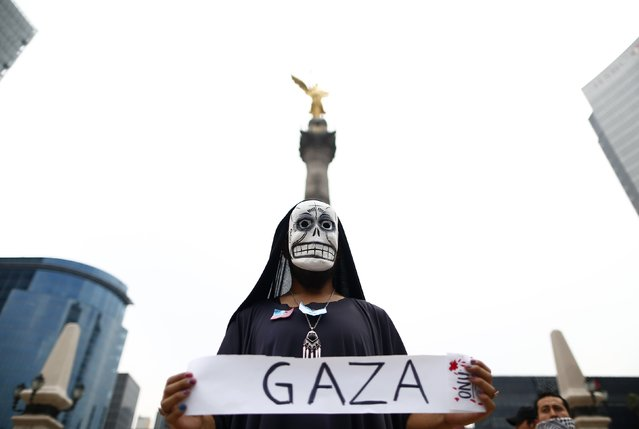A protester wears a skeleton mask during a protest, against Israeli military action in Gaza, while standing underneath the Angel of Independence in Mexico City  August 9, 2014. Israel launched more than 30 air attacks in Gaza on Saturday, killing nine Palestinians, and militants fired rockets at Israel as the conflict entered a second month, defying international efforts to revive a ceasefire. (Photo by Edgard Garrido/Reuters)