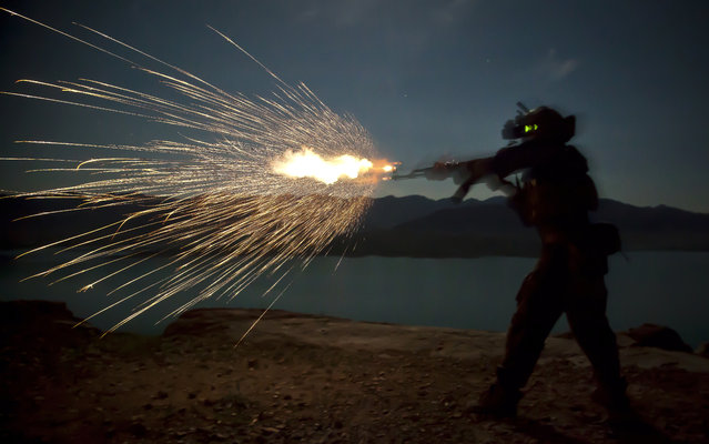 A Marine Special Operations Team member fires an AK-47 during night fire sustainment training in Helmand province, Afghanistan, March 28, 2013. Marine Special Operations Team members are deployed in Helmand province to train and mentor Afghan National Security Forces. (Photo by Sgt. Pete Thibodeau/U.S. Marine Corps photo)