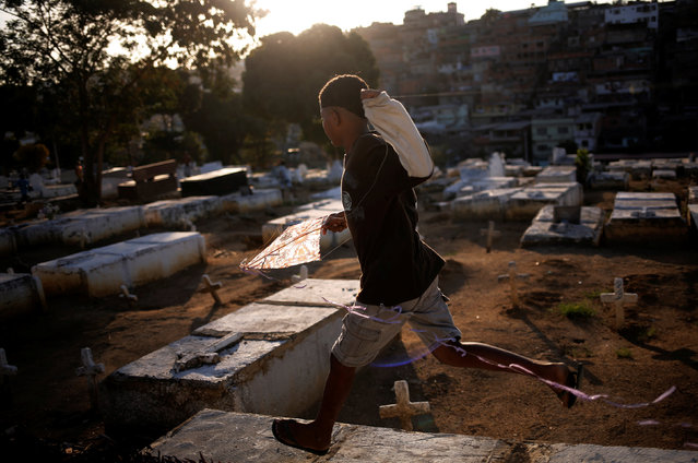 A boy runs as he holds his kite in a cemetery in the Vila Operaria Favela of Rio de Janeiro, Brazil, July 9, 2016. (Photo by Nacho Doce/Reuters)