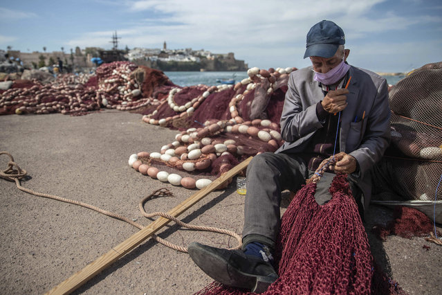 A fisherman named Hassan wears a compulsory face mask while mending a net during a state of emergency and home confinement orders due to coronavirus, in Rabat, Morocco, Tuesday, April 7, 2020. (Photo by Mosa'ab Elshamy/AP Photo)