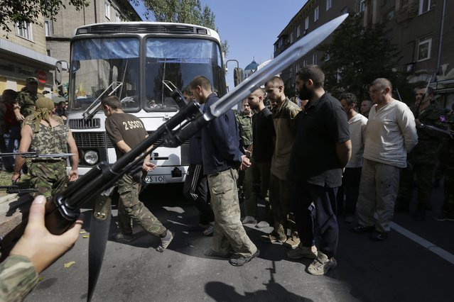 Pro-Russian rebels escort captured Ukrainian army prisoners in a central square in Donetsk, eastern Ukraine, Sunday, Aug. 24, 2014. (Photo by Sergei Grits/AP Photo)