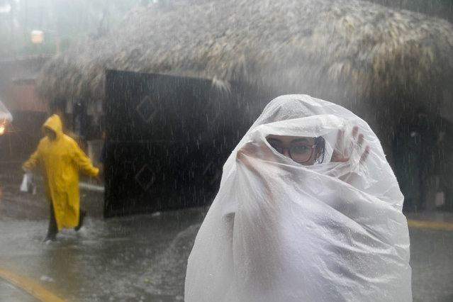 A woman covers herself with a plastic bag as she makes her way to work as Hurricane Maria approaches the coast of Bavaro, Dominican Republic, Wednesday, September 20, 2017. (Photo by Tatiana Fernandez/AP Photo)