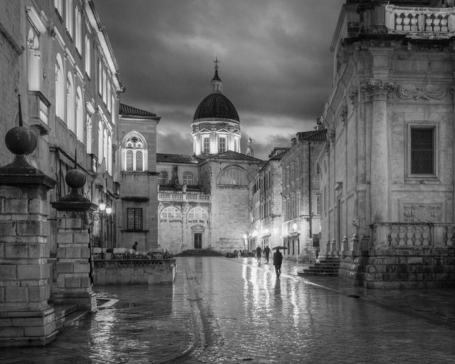 """""""I got up early every morning to capture the good light and the city coming to life"""", wrote Douglas E Finstad, 57, in his submission taken in Croatia. """"On this morning it was pouring rain and very miserable. I ducked under an overhang and set up to capture the image of workers making their way through the rain to work"""". (Photo by Douglas E Finstad)"""