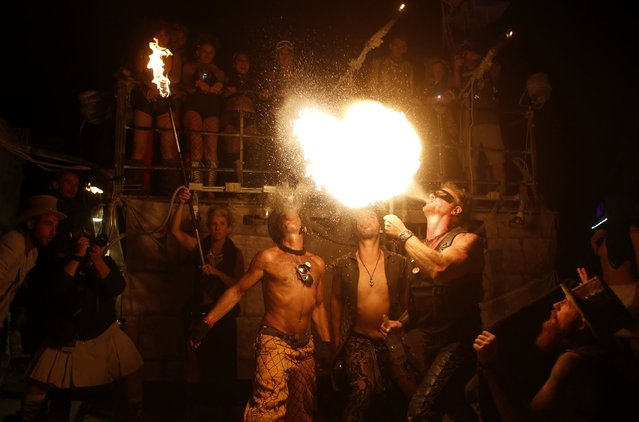 "Participants blow flames during the Burning Man 2014 ""Caravansary"" arts and music festival in the Black Rock Desert of Nevada, August 30, 2014. (Photo by Jim Urquhart/Reuters)"