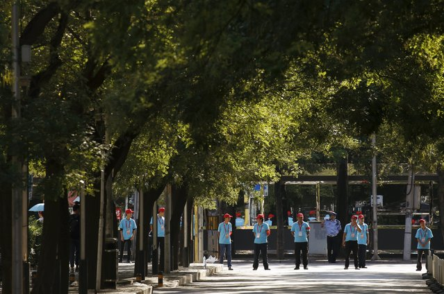 Security volunteers stand guard near the Changan Avenue, ahead of the military parade to mark the 70th anniversary of the end of World War Two, in Beijing, China, September 3, 2015. (Photo by Kim Kyung-Hoon/Reuters)