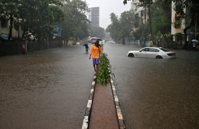 A girl walks on a pavement in a waterlogged street as the rain falls in Mumbai, India on September 19, 2017. (Photo by Shailesh Andrade/Reuters)