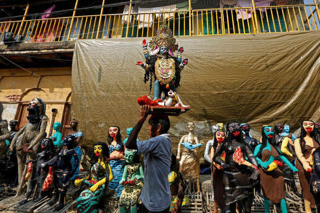 """A man carries an idol of Hindu goddess Kali towards a pandal or a temporary platform, as he walks past the clay idols of the mythological characters """"Dakinis"""" and """"Yoginis"""", who will be worshipped along with the goddess Kali during the Kali Puja festival in Kolkata, October 17, 2017. (Photo by Rupak De Chowdhuri/Reuters)"""