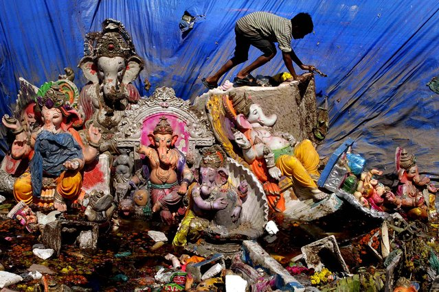 A boy searches for reusable items amid idols of the Hindu  god Ganesh left a day after the immersion of idols in Ahmadabad, India, on September 30, 2012. Every year millions of devout Hindus immerse Ganesh idols into oceans and rivers during the ten-day long Ganesh Chaturthi festival that celebrates the birth of the Hindu god. (Photo by Ajit Solanki/Associated Press)