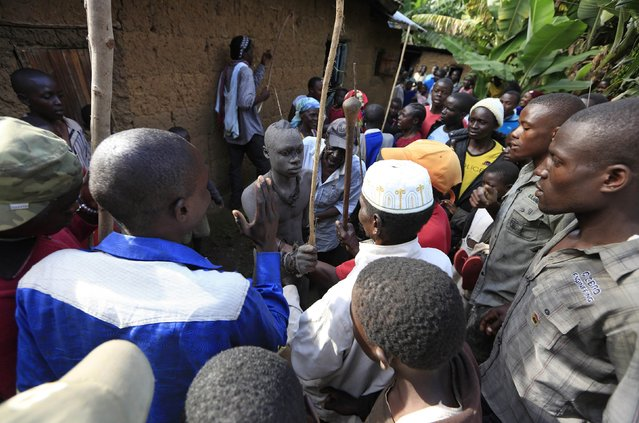People crowd around a Bukusu youth who just underwent circumcision outside a house in Kenya's western region of Bungoma August 9, 2014. (Photo by Noor Khamis/Reuters)