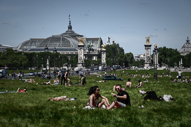 People enjoy a sunny day on a loan near the Grand Palais and the Pont Alexandre III bridge in Paris on May 20, 2020 as France partially lifted restrictions to prevent the spread of the COVID-19 disease caused by the novel coronavirus. (Photo by Philippe Lopez/AFP Photo)