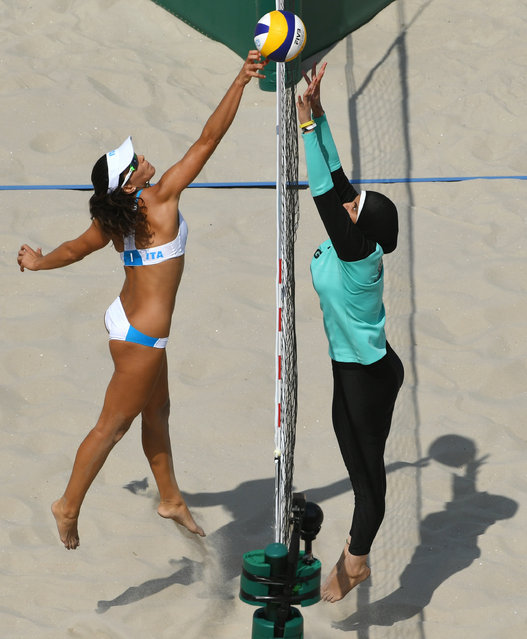 Italy's Marta Menegatti (L) jumps for the ball during the women's beach volleyball qualifying match between Italy and Egypt at the Beach Volley Arena in Rio de Janeiro on August 9, 2016, for the Rio 2016 Olympic Games. (Photo by Yasuyoshi Chiba/AFP Photo)