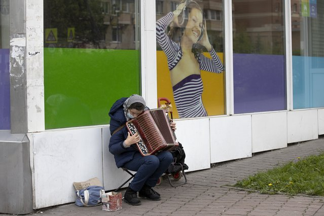 A woman wearing a face mask to protect to coronavirus plays accordion to get some money in Mytishchi, just outside Moscow, Russia, Wednesday, May 27, 2020.  The coronavirus outbreak has badly hurt Russia's economy, already weakened by a drop in global oil prices and Western sanctions. According to government statistics, unemployment has jumped to 4.3 million people in April, the highest number since 2016. (Photo by Alexander Zemlianichenko/AP Photo)