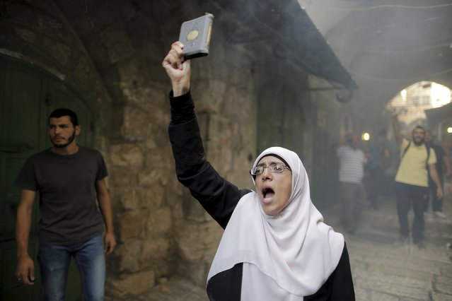 A Palestinian woman shouts slogans as she holds a Koran during clashes with Israeli police forces in Jerusalem's Old City September 13, 2015. Israeli police raided the plaza outside Jerusalem's al-Aqsa mosque on Sunday in what they said was a bid to head off Palestinian attempts to disrupt visits by Jews and foreign tourists on the eve of the Jewish New Year. (Photo by Ammar Awad/Reuters)