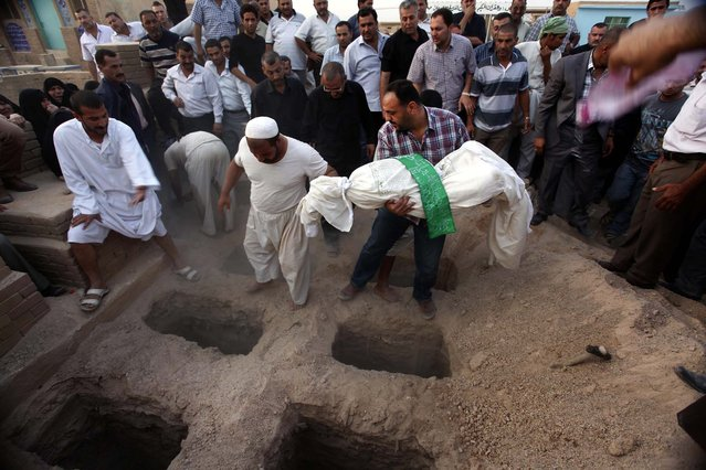 A relative buries Zahra Hadi, 17, in Najaf, 100 miles south of Baghdad, Iraq October 24, 2012. A family of six was killed when a series of attacks struck Shiite neighborhoods in Baghdad early on Tuesday, killing a total of nine people and wounding 26 others, according to Iraqi officials. (Photo by Alaa al-Marjani/Associated Press)