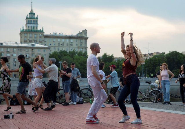 People dance on the first day that lockdown measures were eased at an embankment over the Moscow River in Moscow, Russia, Tuesday, June 9, 2020. The Russian capital on Tuesday has ended a tight lockdown in place since late March, citing a slowdown in the coronavirus outbreak. Starting from Tuesday, Moscow residents are no longer required to self-isolate at home or obtain electronic passes for traveling around the city. (Photo by Pavel Golovkin/AP Photo)