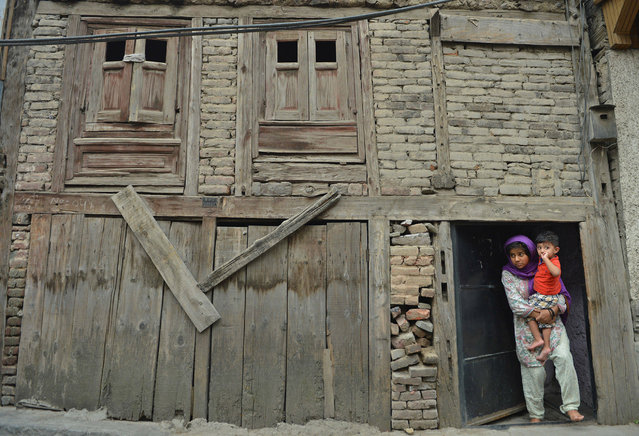 A Kashmiri girl holds her brother in the doorway of their home while watching protesters shout pro-freedom and anti-Indian slogans during  mourning and protests held in downtown Srinagar on August 22, 2016, following the killing of teenager Irfan Ahmed by security forces. Teenager Irfan Ahmed was killed after he was hit in the chest by a teargas canister fired by Indian security forces to quell pro-freedom protests in the Kashmiri capital on August 21. More than 60 civilians have been killed in clashes between protesters and security forces, and thousands more injured in the worst violence to hit the Himalayan region since 201. Indian-administered Kashmir has been in the grip of almost daily anti-India protests and rolling curfews sparked by the killing on July 8 of a popular rebel leader, Burhan Wani, in a gunfight with government forces. (Photo by Tauseef Mustafa/AFP Photo)