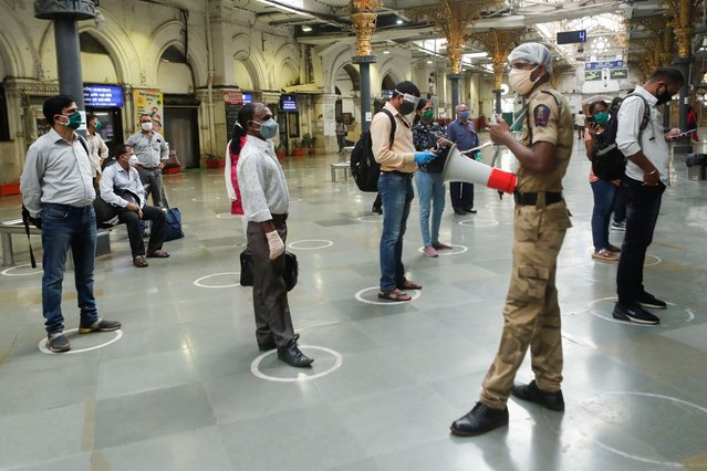 A railway police official makes an announcement on a loudspeaker telling commuters to stand inside the designated circles to maintain social distancing as they wait to board a train at a railway station after some restrictions were lifted during a lockdown to slow the spread of the coronavirus disease (COVID-19) in Mumbai, India, June 22, 2020. (Photo by Francis Mascarenhas/Reuters)
