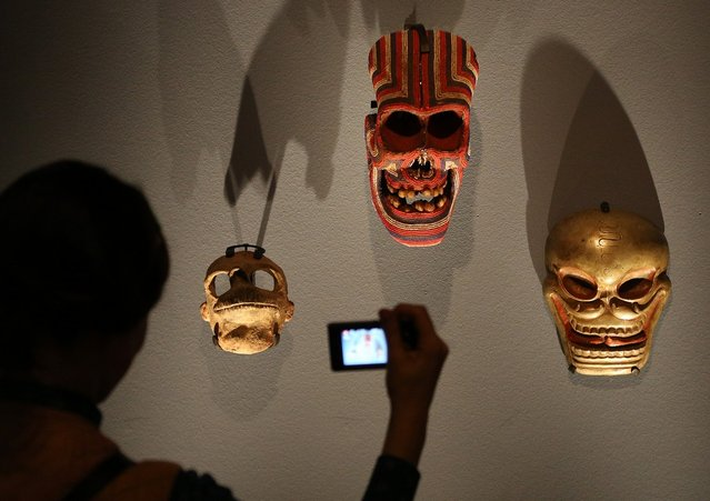 """A visitor photographs Mexican, Tibetan and Cameroonian masks at the """"Death: A Self-portrait"""" exhibition at the Wellcome Collection on November 14, 2012 in London, England. The exhibition showcases 300 works from a unique collection by Richard Harris, a former antique print dealer from Chicago, devoted to the iconography of death. The display highlights art works, historical artifacts, anatomical illustrations and ephemera from around the world and opens on November 15, 2012 until February 24, 2013.  (Photo by Peter Macdiarmid)"""