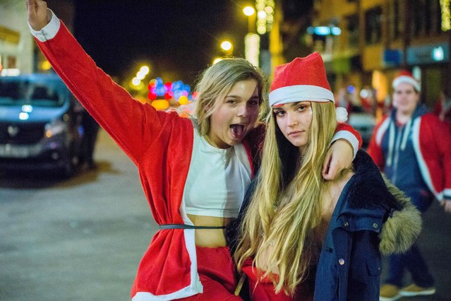 Gifts for the homeless are handed out during Santa Bar Crawl, Oxford, England on December 5, 2017. Here: Oxford university students on a Santa-themed pub crawl. (Photo by Greg Blatchford/Rex Features/Shutterstock)