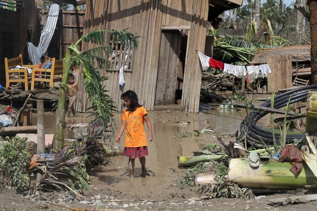 Children walk in front of their flooded home in the aftermath of Typhoon Bopha in New Bataan, Compostela Valley in the southern Philippines on December 5, 2012. The death toll from a typhoon that ravaged the Philippines jumped to 238 on December 5 with hundreds missing, as rescuers battled to reach areas cut off by floods and mudslides, officials said. (Photo by Karlos Manlupig/AFP Photo)