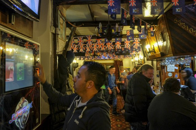 Jukebox tunes are chosen as patrons gather to drink and socialize at the Victory Bar on Friday, February 12, 2016, in Stanley, Falkland Islands.  The town is home to a little more than 2,000 of the islands' nearly 3,000 people. The Falkland Islands are a remote territory of Britain, as can be seen from the symbols of its country's flag.  While the islands have been under the control of multiple countries over the years, control was retained by Britain after Argentina invaded and occupied the islands in 1982. (Photo by Jahi Chikwendiu/The Washington Post)