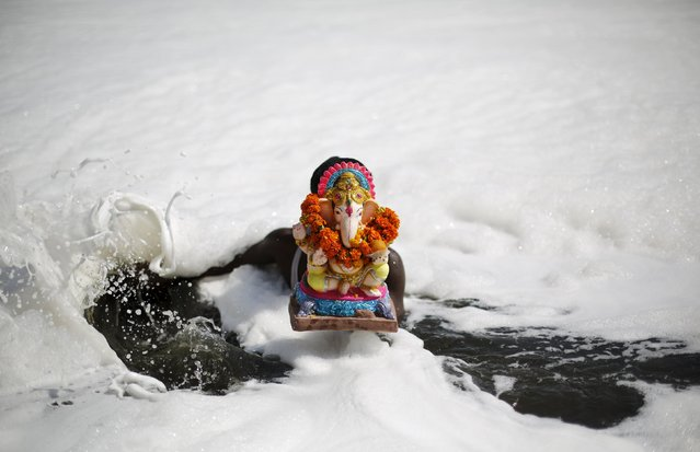 A devotee carries a statue of the Hindu god Ganesh, the deity of prosperity, to be immersed into the polluted waters of the river Yamuna on the last day of the Ganesh Chaturthi festival, in New Delhi, India, September 27, 2015. (Photo by Adnan Abidi/Reuters)