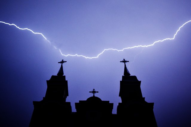 Lightning strikes are seen above a Catholic church during a thunderstorm in the village of Kreva, some 100 km northwest of Minsk, late on June 9, 2020. (Photo by Sergei Gapon/AFP Photo)