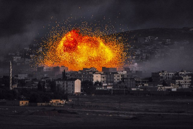 Smoke and flames rise following an explosion in the Syrian town of Kobane, also known as Ain al-Arab, as seen from the southeastern Turkish village of Mursitpinar in the Sanliurfa province on October 20, 2014. Turkey dropped its refusal to allow Kurdish fighters over the border to defend the besieged Syrian town of Kobane, saying it was now helping Iraqi peshmerga to cross the frontier in a major policy shift. (Photo by Bulent Kilic/AFP Photo)
