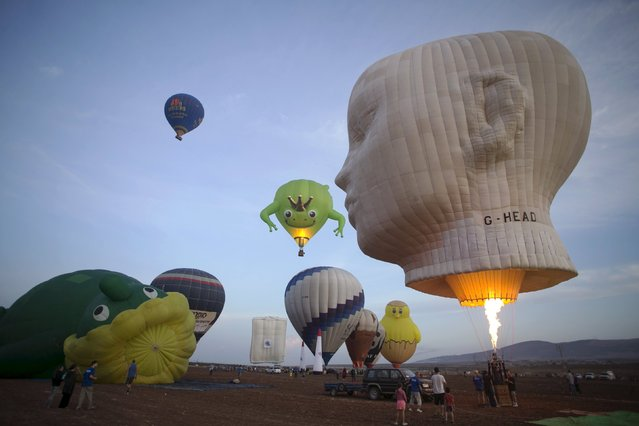 Hot air balloons are prepared for a flight as others take off during an international hot air balloon festival at Maayan Harod National park in northern Israel September 30, 2015. (Photo by Baz Ratner/Reuters)