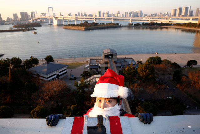 A female window cleaner dressed as Santa Claus prepares to clean a glass window at an event to celebrate the upcoming Christmas at DECKS Tokyo Beach in Tokyo, Japan, December 21, 2017. (Photo by Kim Kyung-Hoon/Reuters)