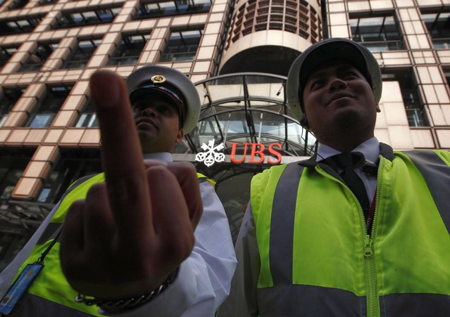 A security guard gestures as he stands with a colleague in front of a UBS bank in the City of London September 15, 2011. News that a single trader had lost Swiss bank UBS around $2 billion in unauthorised deals, and the arrest of 31-year-old Kweku Adoboli in London in connection with the case, stunned the market and sent shares skidding. (Photo by Andrew Winning/Reuters)