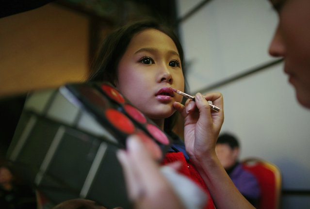 A child model has make-up applied at the backstage during a rehearsal for the Dong Wenmei T100 Children's Collection during China Fashion Week in Beijing October 29, 2014. (Photo by Kim Kyung-Hoon/Reuters)